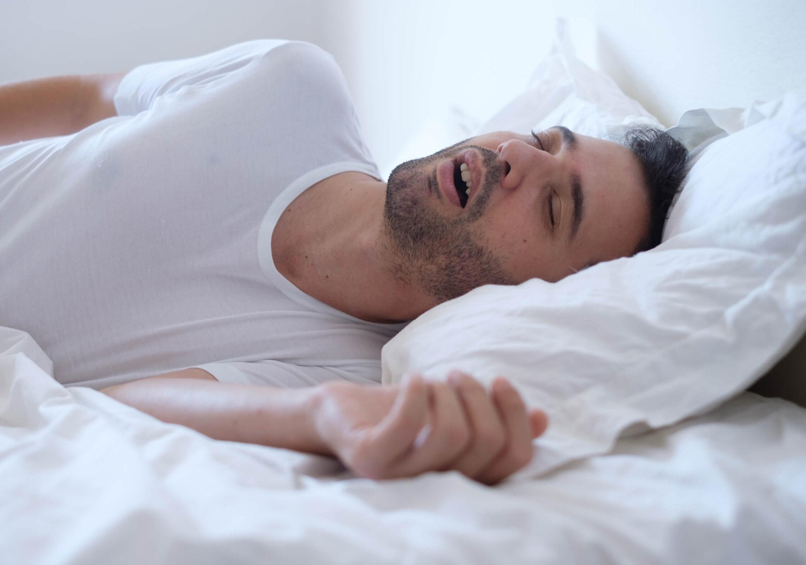 homem na cama com apneia do sono
